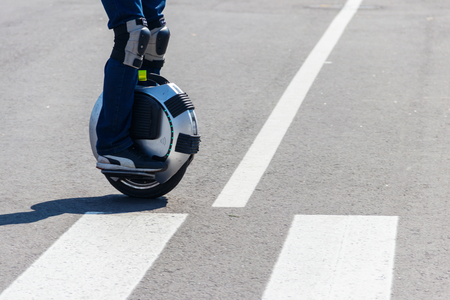 Electric unicycle. Man rides on mono wheel on zebra crossing Banco de Imagens - 115753006