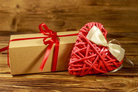Gift box and red heart on wooden background. Valentines day concept