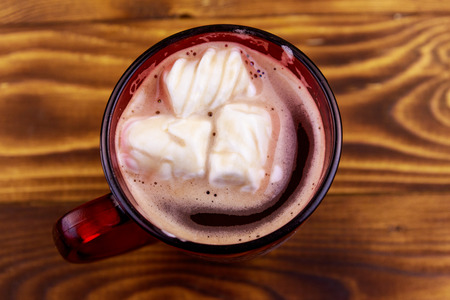 Cup of hot chocolate with melted marshmallow on wooden table