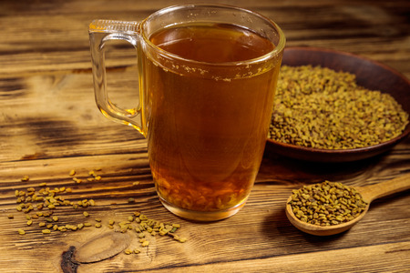 Egyptian yellow tea or Methi Dana drink and fenugreek seeds on wooden table Banque d'images