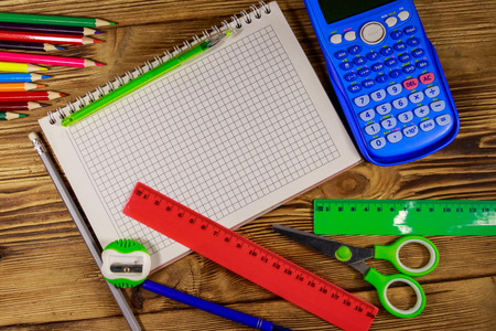 Set of school stationery supplies. Blank notepad, calculator, rulers, pencils, pens, scissors and sharpener on wooden desk. Top view