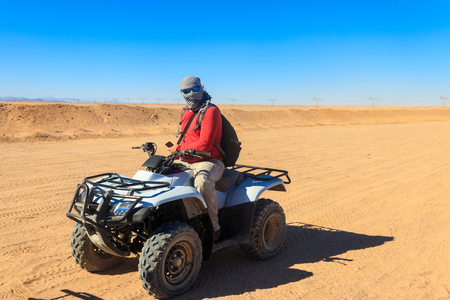 Young man in safari trip through egyptian desert driving ATV. Quad bikes safari in the desert near Hurghada, Egypt
