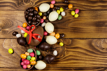 Easter composition with chocolate eggs on wooden background. Top view, copy space Stock Photo