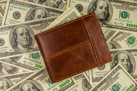 Brown leather wallet on the american one hundred dollar bills background