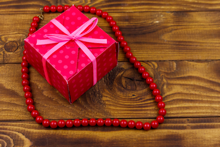Gift box and red beads necklace on wooden background