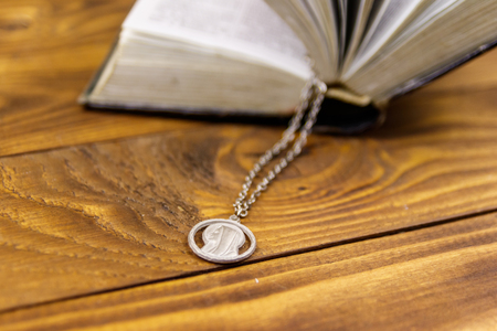 Open Holy Bible with Virgin Mary pendant on wooden background