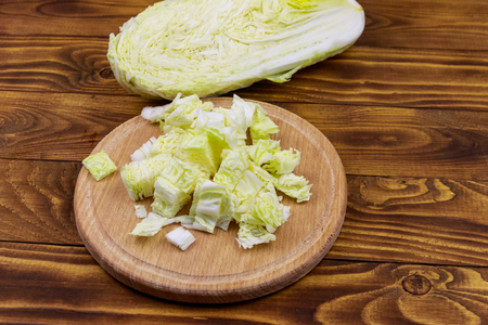 Chopped chinese cabbage on cutting board on wooden table Banque d'images