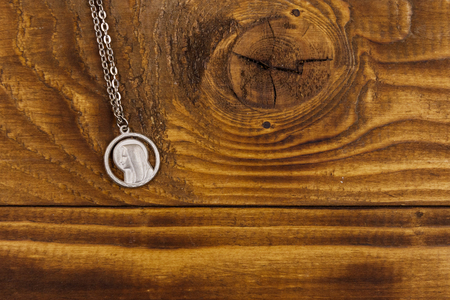 Virgin Mary pendant on wooden background. Top view, copy space