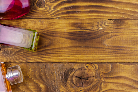 Different bottles of perfume on the wooden background. Top view, copy space