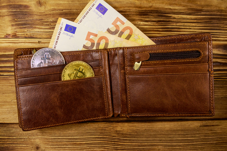 Wallet with fifty euro bills and bitcoins on wooden background Banco de Imagens