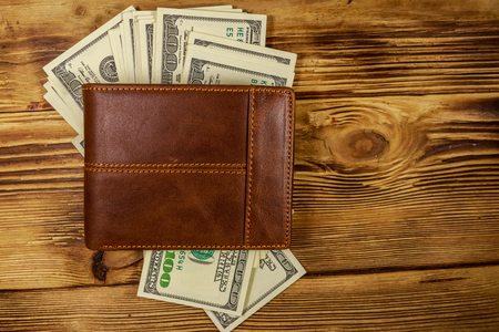 Brown leather wallet and american dollars on wooden table. Top view