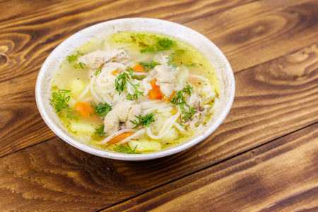 Chicken soup with noodles and vegetables on wooden table