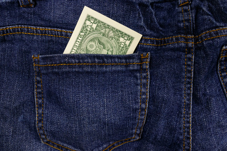 One dollar bill in a pocket of blue jeans