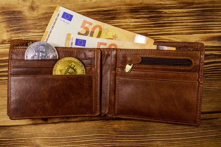 Wallet with fifty euro bills and bitcoins on wooden background Stock Photo