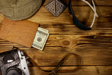 Travel vacation concept. Retro photo camera, hat, sunglasses, souvenir pyramid and passport with money on wooden background. Travel to Egypt. Top view, flat lay