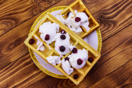 Belgian waffles with ice cream and blackberries on wooden table