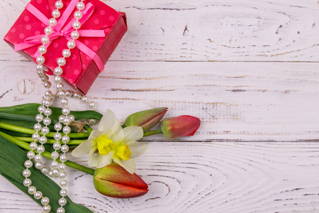 Gift box, pearl necklace and bouquet of red tulips and daffodils on wooden background. Concept of Valentine's Day, Women's Day, Mother's Day and Birthday. Top view, copy space