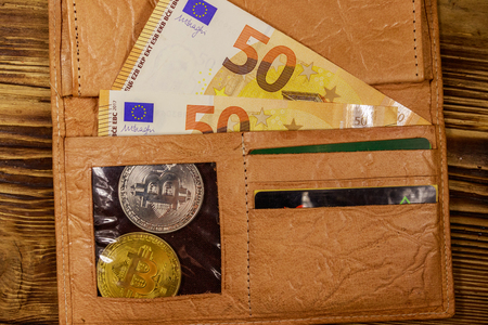Wallet with fifty euro bills and bitcoins on wooden background Reklamní fotografie
