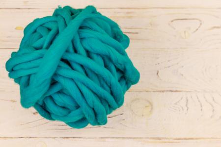 Merino wool yarn ball on white wooden background. Top view