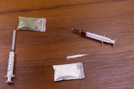 Different type of drugs: cocaine, heroin syringe and dried cannabis on a table. Drug use, crime and addiction concept Stock Photo