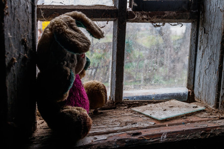 Old dirty stuffed toy rabbit on a windowsill in abandoned house