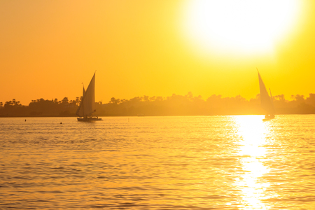 View of the Nile river with sailboats at sunset in Luxor, Egypt