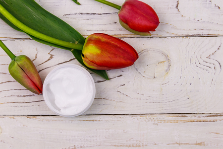 Jar of moisturizer cream with red tulips on white wooden background. Top view, copy space