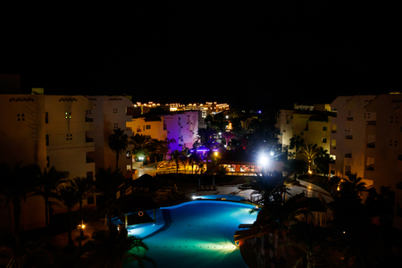 Night view of the modern blue water swimming pool in tropical resort. View from above Reklamní fotografie