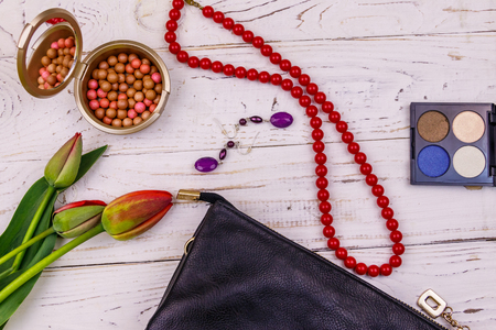 Women accessories and make-up cosmetics on white wooden background. Clutch bag, eye shadow, rouge balls, necklace, earrings and red tulips. Beauty and fashion composition. Top view, flat lay Фото со стока