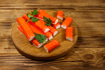 Crab sticks on cutting board on wooden table