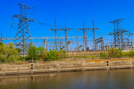 High voltage power lines towers on a riverbank Archivio Fotografico