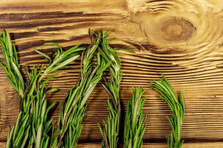 Fresh rosemary herbs on a wooden table. Top view Stockfoto