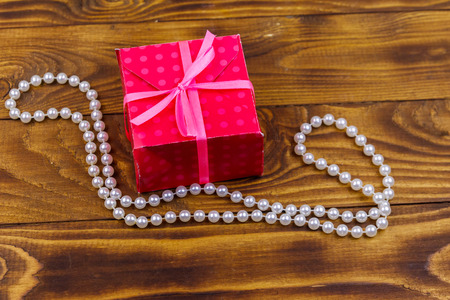 Gift box and pearl necklace on wooden background
