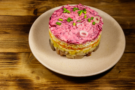 Traditional russian salad Herring under a fur coat (shuba) on wooden table. Layered salad with herring, beets, carrots, onions, potatoes and eggs