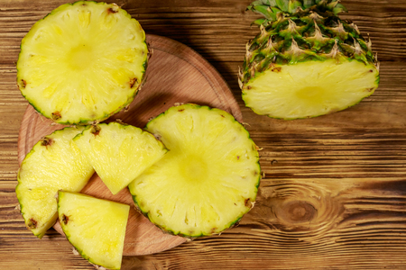 Fresh pineapple on wooden table. Top view Imagens