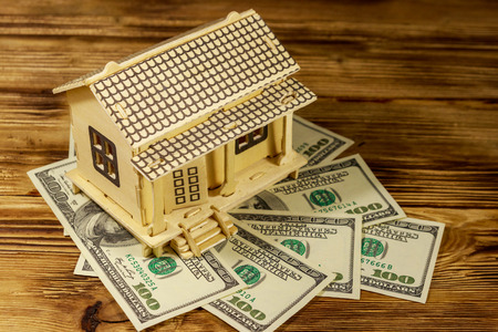 House model and U.S. one hundred dollar bills on wooden background. Property investment, home loan, house mortgage, real estate concept Reklamní fotografie