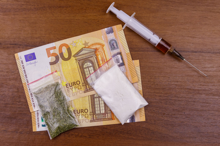 Different type of drugs: cocaine, heroin syringe and dried cannabis and euros on a table. Drug use, drug trafficking, crime and addiction concept