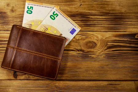 Wallet and fifty euro banknotes on wooden background Stock Photo