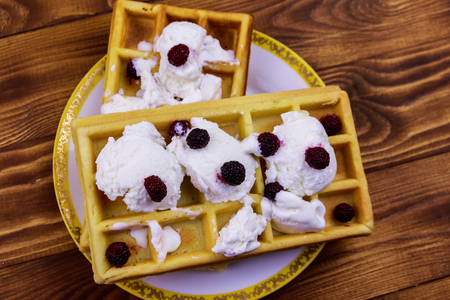 Belgian waffles with ice cream and blackberries on wooden table Banque d'images - 124773003