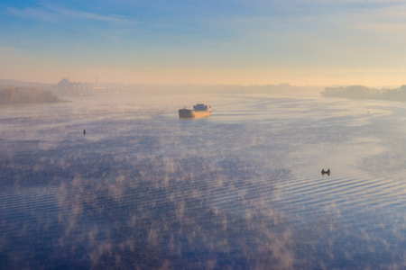 Industrial ship sailing down the river in the mist at morning