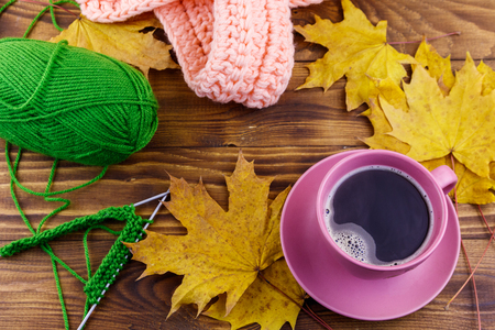 Cup of coffee, ball of yarn, knitting, knitted scarf and yellow maple leaves on wooden table. Autumn still life