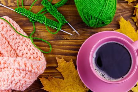 Cup of coffee, ball of yarn, knitting, knitted scarf and yellow maple leaves on wooden table. Autumn still life Stock Photo - 124773024