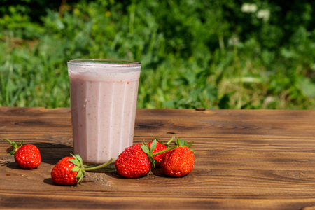 Glass of fresh strawberry smoothie on a wooden table outdoor