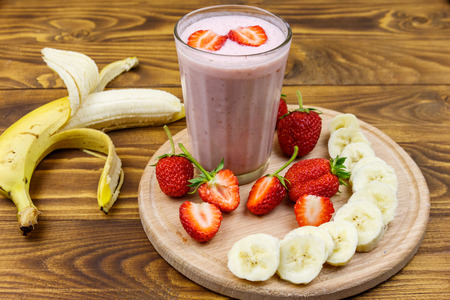 Glass of fresh smoothie of strawberry and banana on a wooden table Reklamní fotografie