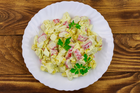 Salad with crab sticks, sweet corn, chinese cabbage, eggs and mayonnaise on wooden table Stok Fotoğraf - 124773047