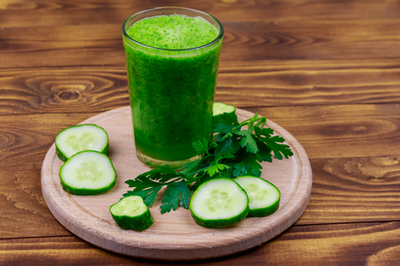 Glass of green detox smoothie of cucumber and parsley on a wooden table Stock Photo