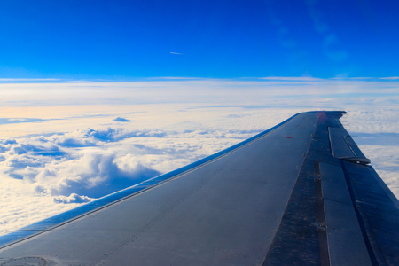 Wing of airplane flying above the clouds in the blue sky 写真素材