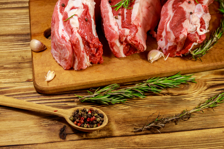 Raw pork ribs with spices, garlic and rosemary on wooden table
