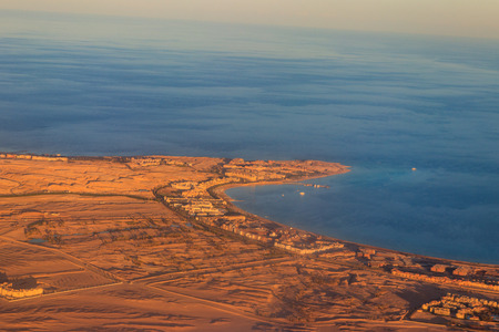 Aerial view on Red sea, Arabian desert and touristic resort near Hurghada, Egypt. View from airplane