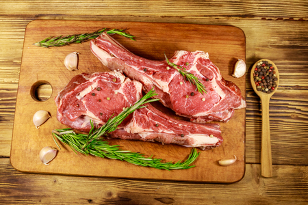 Raw fresh beef rib eye steak on bone with spices, garlic and rosemary on wooden table. Top view